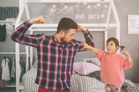 La piccola figlia carina e il suo bel giovane papà stanno giocando insieme nella stanza dei bambini. Papà e bambino trascorrono del tempo insieme seduti sul pavimento in camera da letto. Archivio Fotografico