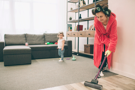 mother and baby together engaged in housework. She is washing the floor of the mop. Housewife and kid doing homework. Woman with little child in the living room. Homemaker doing many tasks while looks after her infant Standard-Bild