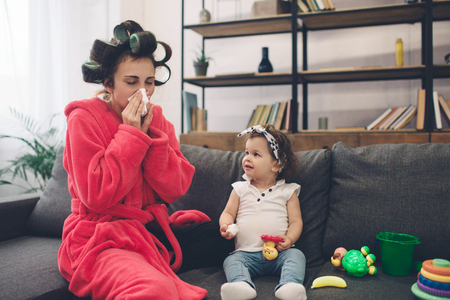 Young mother old is experiencing postnatal depression. Sad and tired woman with PPD. She does not want to play with her daughter. The woman is sick and she has a runny nose. Stock Photo