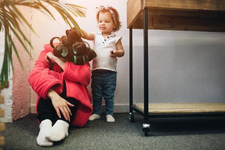 Junge Mutter alt leidet unter einer postnatalen Depression. Traurige und müde Frau mit PPD. Sie will nicht mit ihrer Tochter spielen Standard-Bild