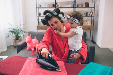 mãe e bebê juntos engajados em trabalhos domésticos Roupas de passar roupa. Dona de casa e garoto fazendo lição de casa. Mulher com criança pequena na sala de estar. Homemaker fazendo muitas tarefas enquanto cuida de seu bebê