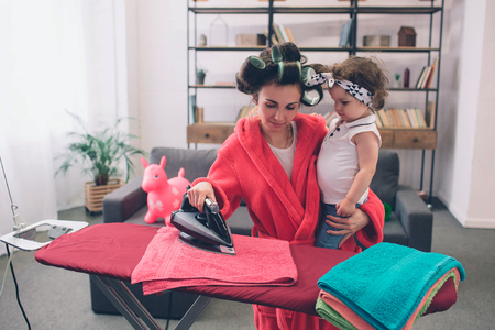 mother and baby together engaged in housework Ironing clothes . Housewife and kid doing homework. Woman with little child in the living room. Homemaker doing many tasks while looks after her infant