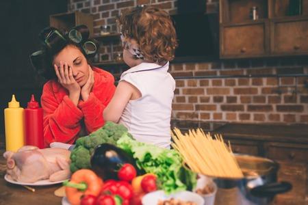 Mãe estressada em casa. Matriz nova com a criança pequena na cozinha home. Mulher fazendo muitas tarefas enquanto cuida de seu bebê Foto de archivo