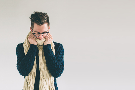 Young man in sweater feel cold over a white background. Stock Photo