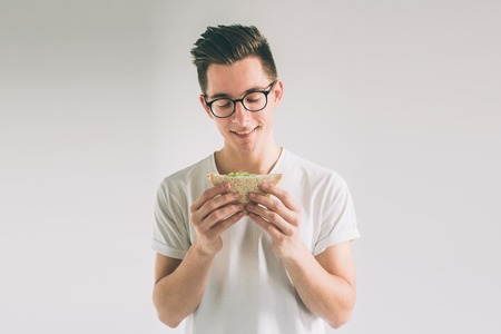 man holding a piece of hamburger. student eats fast food. not helpful food. very hungry man. Nerd is wearing glasses. Zdjęcie Seryjne - 93552234