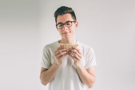 man holding a piece of hamburger. student eats fast food. not helpful food. very hungry man. Nerd is wearing glasses. Zdjęcie Seryjne