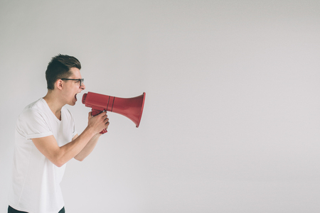 portrait of young man shouting using megaphone over background Nerd is wearing glasses. Stok Fotoğraf