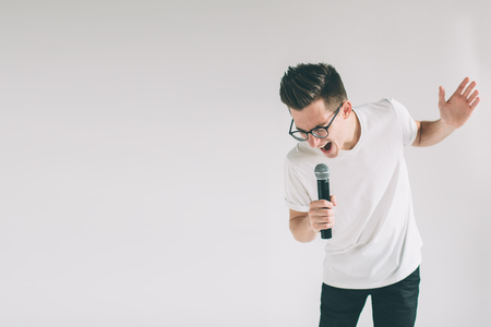 Boy Rocking Out. Image of a handsome man singing to the microphone, isolated on light.