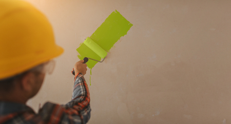 The builder works at the construction site and measures the ceiling. A worker in an orange helmet and a paint roller paints the wall.