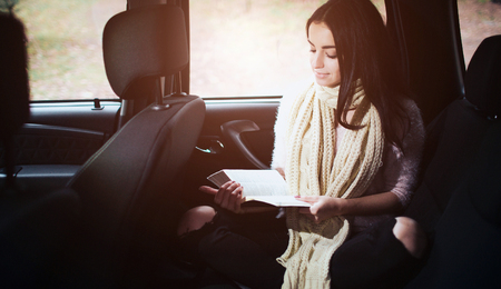 Woman in the car, autumn fall concept. Smiling pretty girl reading a book moving in car.