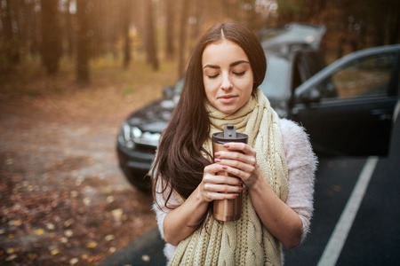 Woman holding disposable cup of coffee beside car. Close up Hand. Autumn concept. Autumn forest journey by car