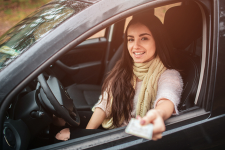 Woman showing driving license. Close up Hand. Autumn concept. Autumn forest journey by car