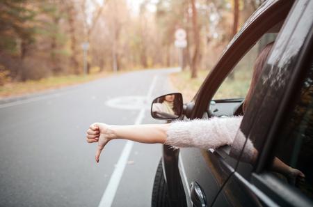 親指を押し下げて道路上の女性旅行者。秋の休暇、休日、旅行、ロードトリップと人々の概念 写真素材