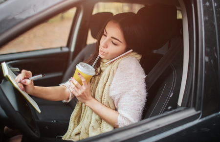 Pretty woman eating food and driving in her car. Stockfoto