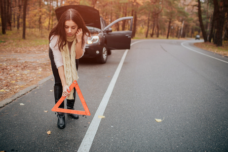 Auto assistance and insurance, troubles while traveling concept. Broken car and auto triangle on road, woman waiting for help
