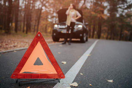 Auto assistance and insurance, troubles while traveling concept. Broken car and auto on road, woman waiting for help Imagens