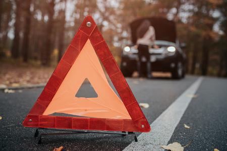 自動車アシスタンスや保険、旅行中のトラブルコンセプト。道路上の壊れた車と車、助けを待っている女性