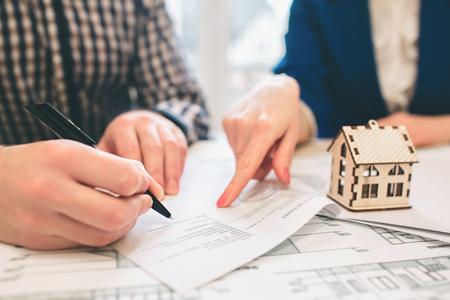 Junge Familienpaare kaufen Mietgrundstückimmobilien. Agent gibt Beratung für Mann und Frau. Vertragsunterzeichnung für den Kauf eines Hauses oder einer Wohnung. Unterzeichnen Sie einen Vertrag oder eine Vereinbarung. Geschäftsdokumentation