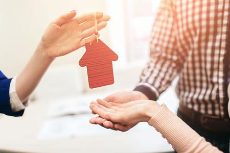 Junge Familienpaare kaufen Mietgrundstückimmobilien. Agent gibt Beratung für Mann und Frau. Vertragsunterzeichnung für den Kauf von Haus oder Wohnung oder Wohnung. Er hält ein Modell des Hauses in Händen