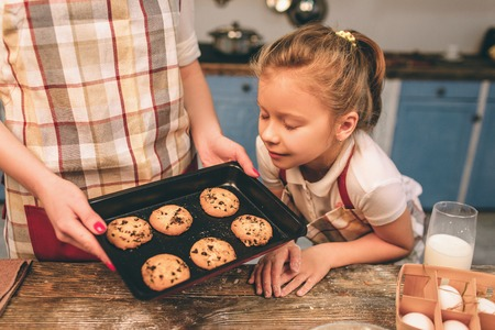 Cooking homemade cakes. Happy loving family are preparing bakery together. Mother and child daughter girl are cooking cookies and having fun in the kitchen. Baby sniffing cookies Stock Photo