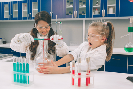 Two little kids in lab coat learning chemistry in school laboratory. Young scientists in protective glasses making experiment in lab or chemical cabinet. Studying ingredients for experiments .
