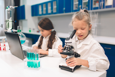 Two little kids in lab coat learning chemistry in school laboratory. Young scientists in protective glasses making experiment in lab or chemical cabinet. Working on a pc