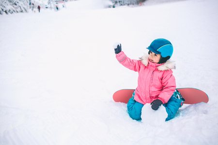 Snowboard Winter Sport. Little kid girl playing with snow wearing warm winter clothes. Winter background