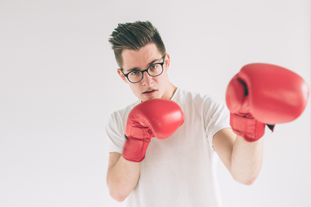 Cowardly funny young man in red boxing gloves. Nerd is wearing glasses.