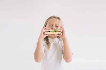 Child holding a piece of hamburger. Kid eats fast food. not helpful food. very hungry baby. Girl isolated on white background.