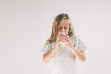 girl is drinking fresh glass of milk isoladed on white background