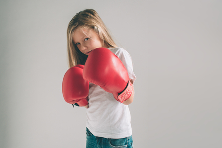 Cowardly funny young girl in red boxing gloves on white background.
