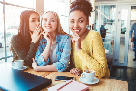 Another picture of three girls gossiping about something. Stock Photo