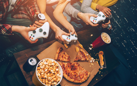 Nice and yummi picture of different types of food and drinks on the table and four wireless gamepads in four paires of hands.