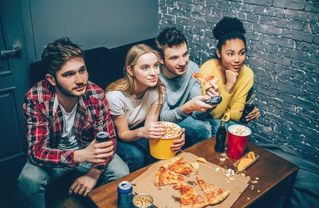 Excited young people are sitting together on a couch, eating popcorn and watching different movies. Stock Photo