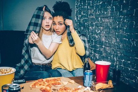 A picture of two girls that are trying to cover themsels with a planket because they are watching a horror movie and they are scared