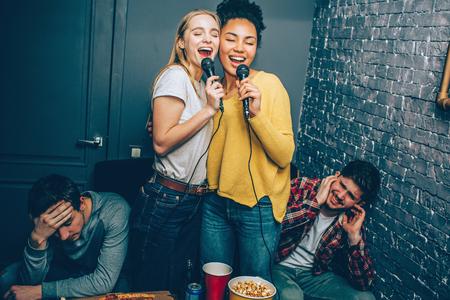 Zwei Mädchen singen sehr laut ein Lied. Ihr Freund mag es nicht, weil junge Frauen überhaupt nicht gut singen.