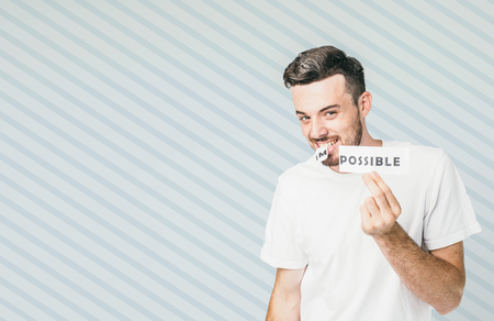 Attractive and positive guy is standing at the white wall and holding a piece of paper in his hand and rest of it with his teeth.