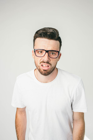 A portait of a guy in white t-shirt and glasses looking straight to camera. His sight is strange and disturbed. Close up.