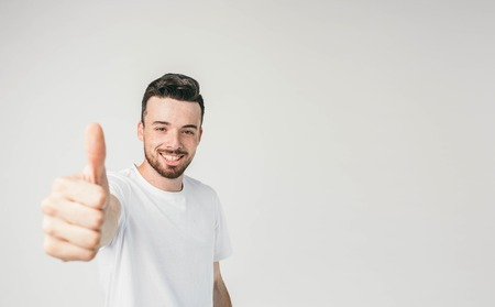 A man standing on the left side of a frame looking straight to the camera and showing his big thumb up to it. He looks cheerful and happy. Reklamní fotografie