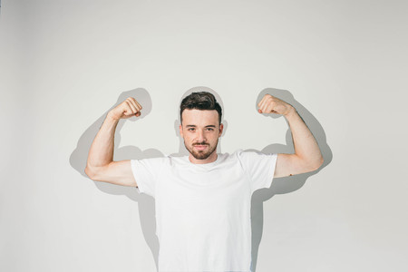 Strong and powerful guy is standing at white wall and posing to camera. He is showing his big muscles and how much strenght does he have. Cut view.
