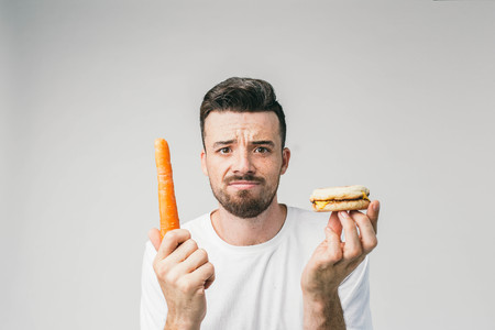 Close up of a bearded guy standing in the white room and holding a carrot in his right hand and a small burger in left hand.