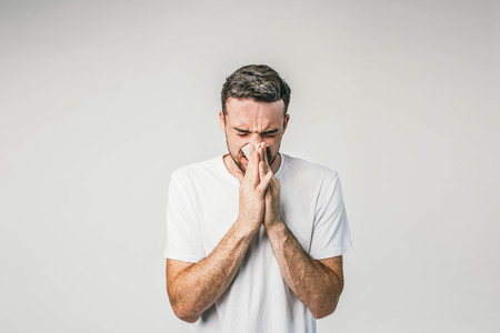 Dark-haired man is standing near the white wall and sneezing. Seems like he caught some cold and soon will be very ill. Stock Photo