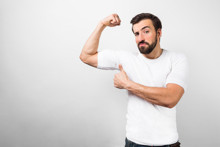 Young man standing isolated on white background in white shirt and showing a big thumb up in front of his arm muscles.