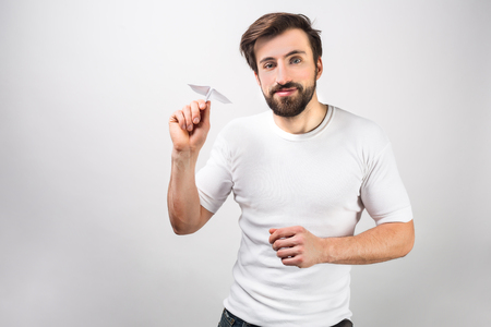 Handsome and happy man in white shirt is standing near the wall and holding a paper airplane. Stock Photo