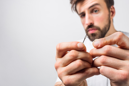 Serious and concentrated guy is trying to put a thread through an eye of a needle.