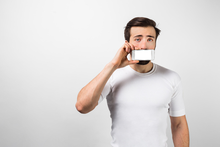 Another picture of dark-haired man standing near white wall and showing bright screen of the phone to camera. Stock Photo
