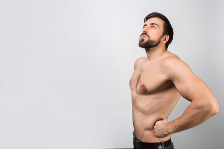 This man is standing without a shirt in a position of a superhero putting his hands on his hips. Stock Photo