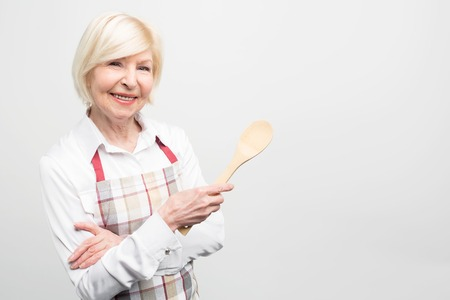 Close up of old woman that likes to spend her free time in kitchen and cook tasty food. She makes delisios meal. Isolated on white background