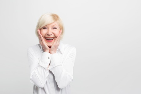 Old but happy woman wears white blouse and showing that she is ery surprised. She has a good luck. Isolated on white background. 版權商用圖片