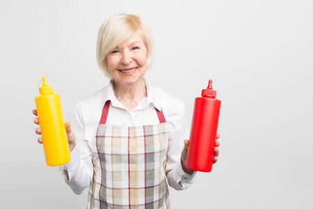Great picture of old woman holding two bottles of sauses in her hands. She want to cook some tasty food for her beloved. Isolated on white background.